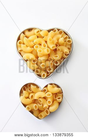 Macaroni dry pasta on the heart shape container
