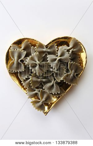 farfalle or farfalloni dry pasta on the heart shape container