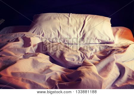 Messy white bed and pillow in the morning vintage or retro color toned