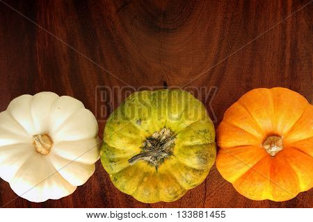 Background pumpkin yellow, green and white on a wooden floor.