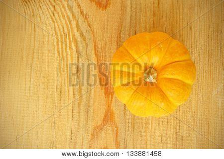 Background yellow pumpkin on a wooden floor