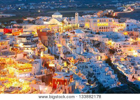 Fira, modern capital of the Greek Aegean island, Santorini, with Orthodox Metropolitan Cathedral at night, Greece