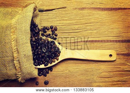 Coffee beans spilling from a burlap bag and a scoop on a textured wood surfacevintage color toned image
