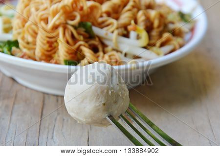 pork ball stab in fork and noodle on dish