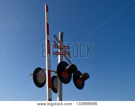 Railroad train crossing sign signal light with clear blue sky background
