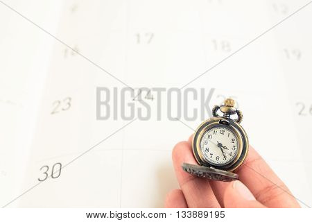 Woman hand hold a classic vintage necklace watch on calendar date paper - concept of time management
