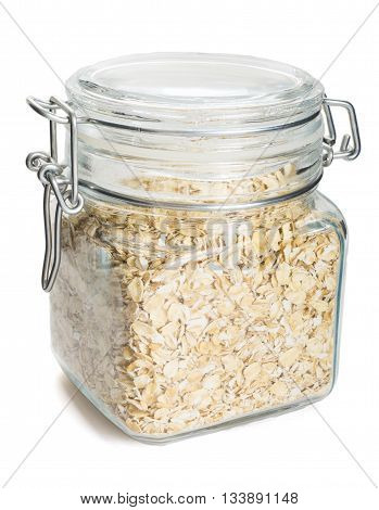 Dry uncooked oat flakes oatmeal in glass transparent jar isolated on white background
