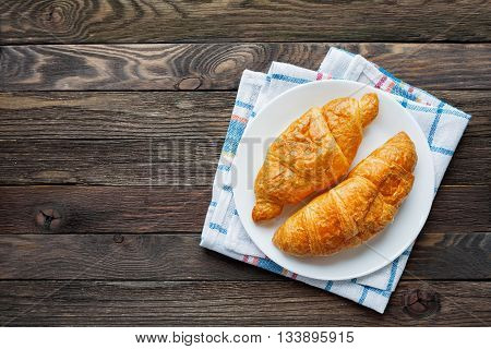Continental breakfast background - pair of croissants on plaid blue napkin. Rustic wooden background with place for text. Top view.