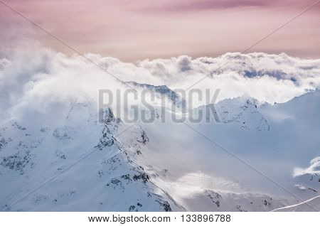 Mountain peaks and clouds at sunset. Beautiful winter landscape