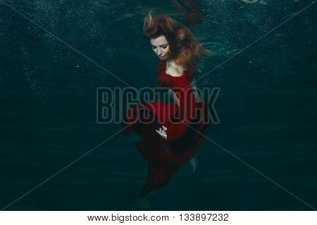 Woman in a red dress under water on the head of her developing hair.