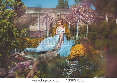 Girl in a long dress sitting among the flowers in the park.