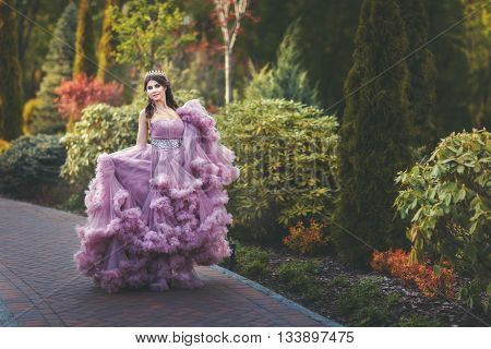Woman with a crown on his head walks in the park she is dressed in a fluffy dress.