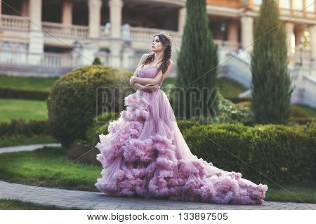 Woman Queen walks in the park she is dressed in luxuriant pink dress.