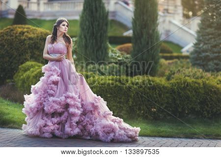 Woman queen she is dressed in luxuriant long pink dress.