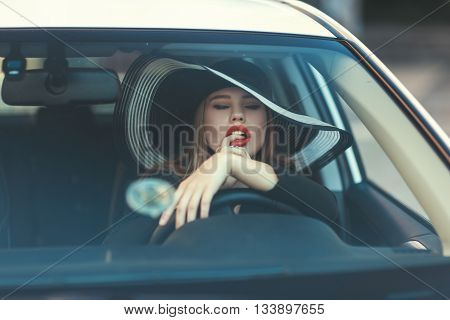 Woman sexually put her finger in her mouth she sits behind the wheel of a car.