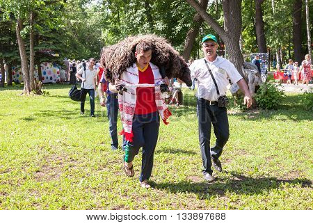 SAMARA RUSSIA - MAY 28 2016: Man carries a sacrificial lamb during the traditional Tatar Sabantuy holiday