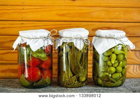 Three clear glass jars of colorful pickled vegetables: tomatoes and cucumbers