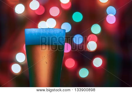 Glass of beer on the bokeh lights background .