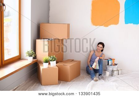 Woman choosing paint colour from swatch for new home sitting on wooden floor