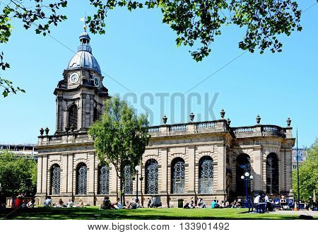 BIRMINGHAM, UNITED KINGDOM - JUNE 6, 2016 - View of St Philips Cathedral with people relaxing in the Summer sunshine in the foreground Birmingham England UK Western Europe, June 6, 2016.