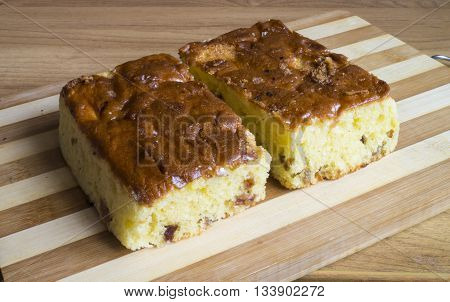 Sweet fruit cake with raisins on striped kitchen board on wooden table