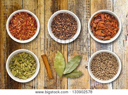 Spices including chilli flakes cloves bird's eye chillies cardamoms cinnamon stick bay leaves and coriander seeds in white pots on a distressed wooden board