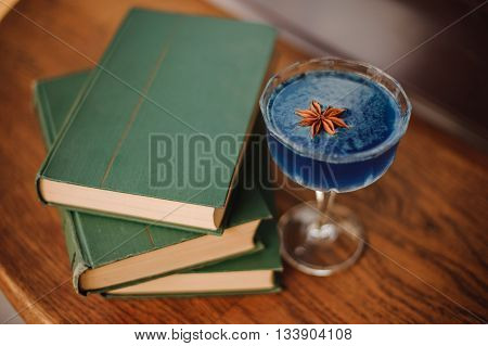 Blue cocktail with Star Anise on bar next to books