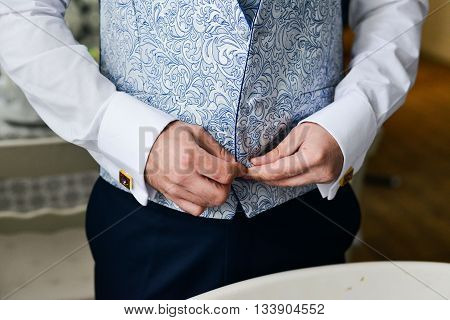 Close-up of a man in a tux fixing his cufflink. groom bow tie cufflinks