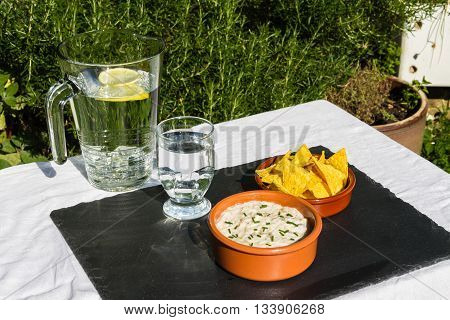 Aubergine Dip In Ceramic Bowl With Tortilla Chips And Iced Water. Outdoors On Slate Mat.