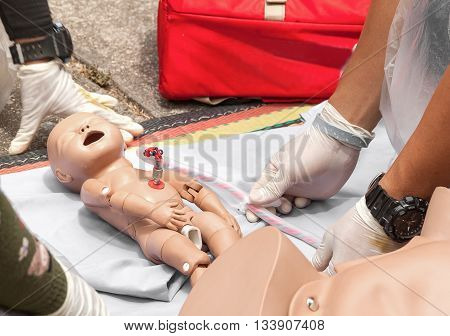 Doctor, paramedic,  The refresher training to assist childbirth newborn with medical baby dummy in emergency the midwife.(select focus baby dummy)