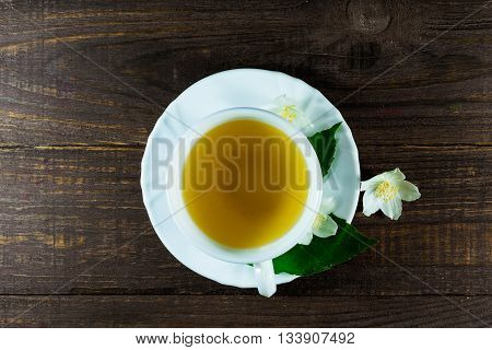 A cup of green jasmine tea standing in the center with white jasmine flowers and green leafs on a wooden background. top view