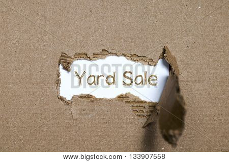 The word yard sale appearing behind torn paper.