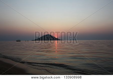 Sunset with lake water lapping in foreground and Thumbi island in the background