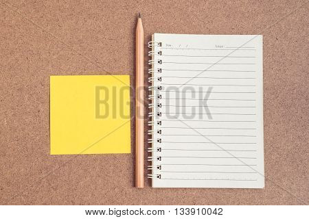 Top view of open spiral notebook empty line paper with brown pencil and yellow sticky notes - notebook paper on brown background