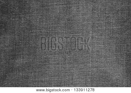 the textured background from denim or rough cotton material of dark gray color
