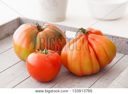 Three different organic tomatoes from Spain on a wooden tray.