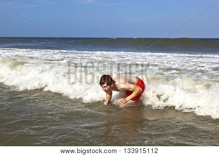 Young Boy Is Body Surfing In The Waves Of The Ocean