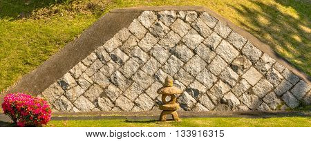 A colorful flowering bush flanks a stone Japanese pagoda statue with a block granite wall in the background
