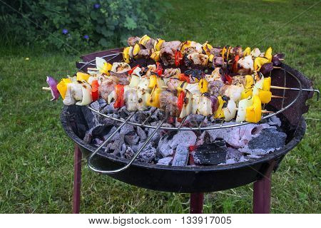 shashlik skewers with onions peppers and meat on a small old barbecue grill in the garden selected focus and very narrow depth of field