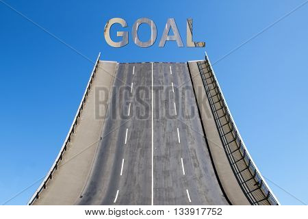 Road leads directly upwards in the blue sky with text GOAL business concept for new goals future and success