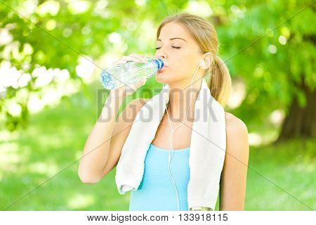 Young woman is drinking water after jogging.
