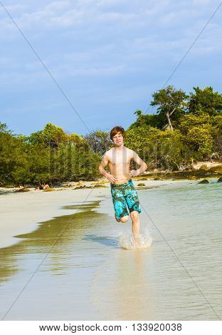 Young Boy With Red Hair Jogging Along The Tropical Beach