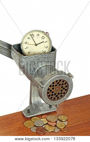 Alarm clock in manual meat grinder and coins on wooden table.Money concept.