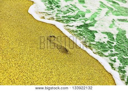 Human trace on sandy beach near turquoise sea surf taken closeup.Toned image.