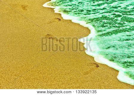 Human traces on sandy beach near turquoise sea surf.Toned image.