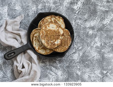 Whole grain vegan pancakes in a cast iron pan on a stone background