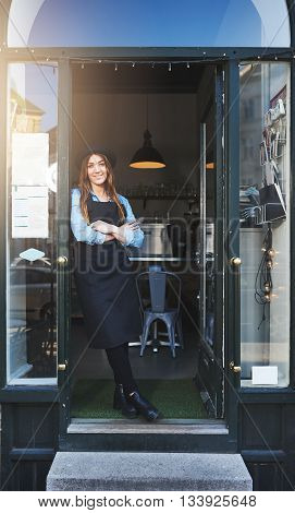 Cheerful Barista Leaning Against Doorway In Cafe
