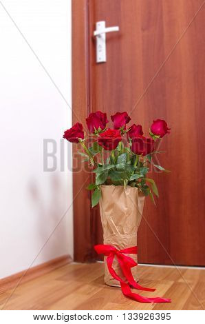 bouquet of red roses next to the door