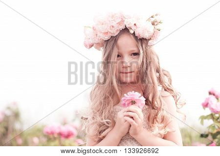 Cute baby girl 3-4 year old holding flower rose outdoors. Child standing in meadow. Looking at camera.