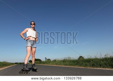 Young woman with rollerblades on a road